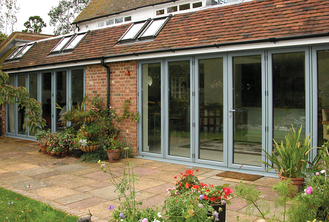 Contemporary styled modern aluminium sliding doors opening onto a beautiful garden with a swimming pool