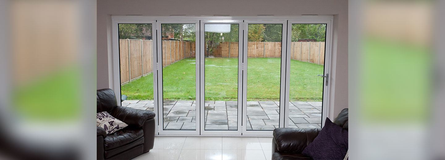 Contemporary white aluminium sliding doors opening onto a garden shown from inside